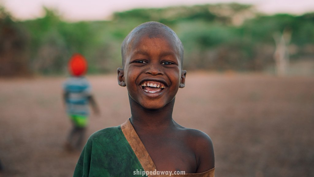 Portraid of a kid with a big smile from the Maasai Samburu tribe in Kenya