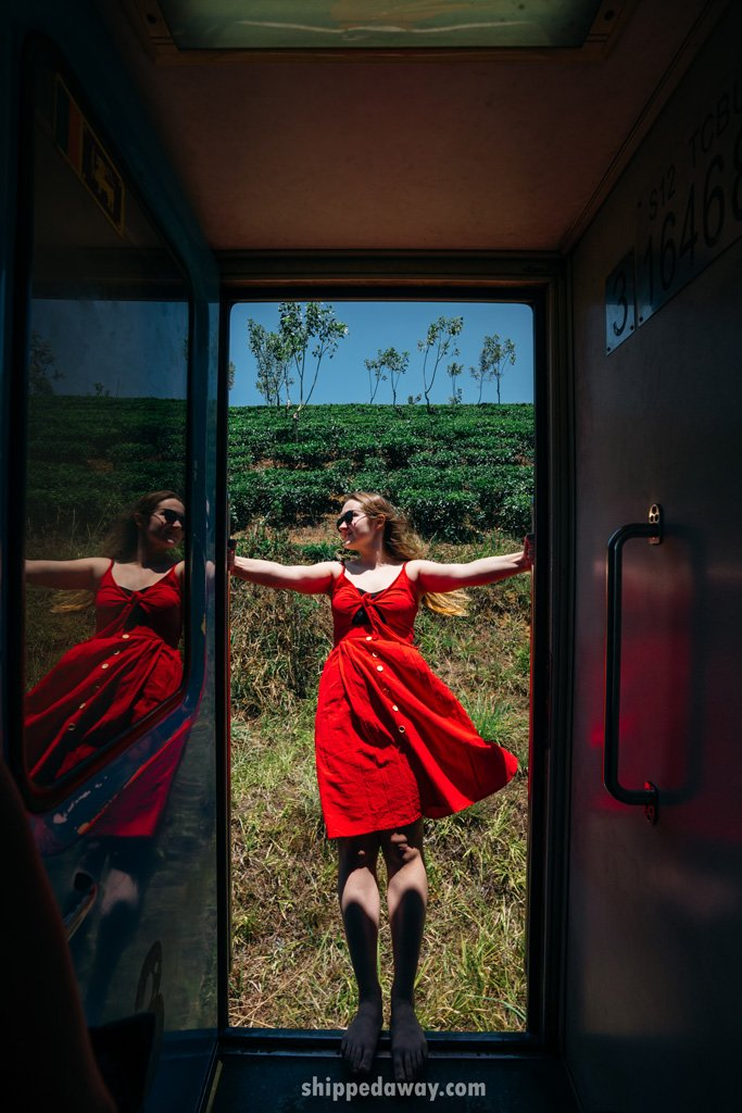 Girl in red dress leaning out of the train in Sri Lanka