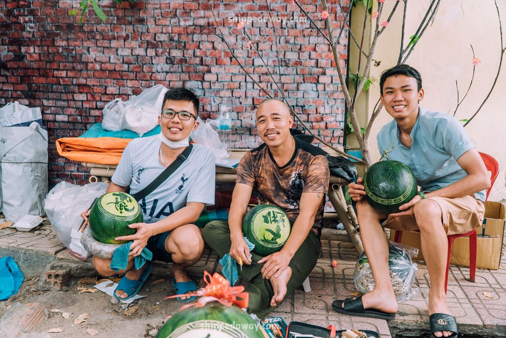 Group of craftsmen on the street carving watermelons for Tet, Vietnamese New Year
