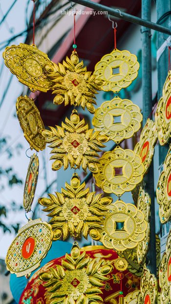 Golden trinkets hanging from a storefront during Tet, Vietnamese New Year